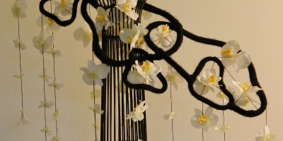 B&W Floating Orchid Fringe: (white orchids strung on a black vertical & transverse structure)